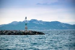 Rusty light tower in the Mediterranean sea in Greece
