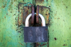 rusty lock on a texture of old, metal, iron, Green, celadon door, which the old paint flaking. place for text.