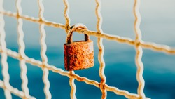 Rusty love padlock hanging on a bridge on a light blue sea background. 16 on 9. Makarska, Croatia