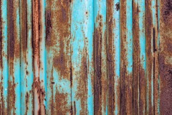 Rusty metal background with old layers of blue paint. Texture rusted shipping container.