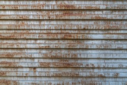 Rusty metal background with old layers of silver paint. Texture rusted shipping container.