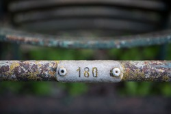Rusty metal bar covered in lichen and moss with number plate screwed onto it engraved with the number 180
