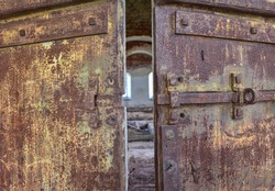 rusty metal door in an abandoned church, entrance to an abandoned temple