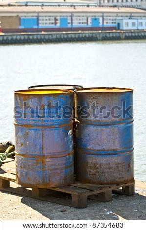 rusty metal oil barrels at shipyard - stock photo