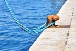 Rusty metal parking bollard with blue rope. Old metal bollard for ships in port