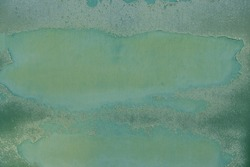 Rusty metal surface with green paint flaking and cracking texture, grunge background.