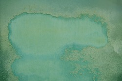 Rusty metal surface with green paint flaking and cracking texture, grunge background. Copy space