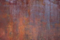 rusty metal surface with red and orange tones - worn irregular steampunk background with scratches for a wallpaper