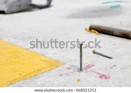 Rusty nails on cement floor In Road Construction
