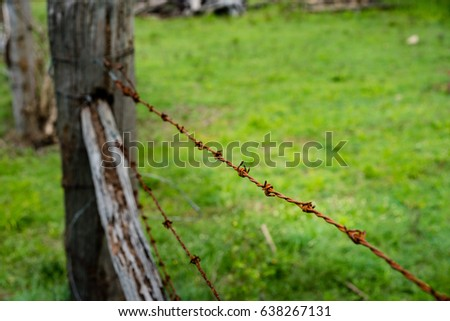 Rusty old barbed-wire fence and wooden posts. Closeup. Blurred background.  Horizontal landscape orientation.  #638267131