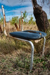 Rusty old broken chair abandoned in the woods. Damaged chair alone under an almond tree among the grass in the countryside