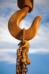 Rusty old crane hook with chains hanging on it. Blue sky background.