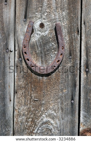 rusty old horseshoe nailed on a wooden door