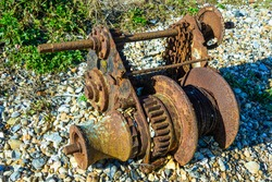 rusty old winch on pebbly beach. relic was used for winching boats up the beach but weathering has corroded the metallic structure