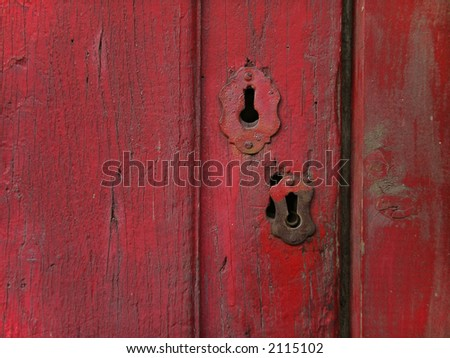 Rusty old wooden door painted in red, with metallic keyhole.