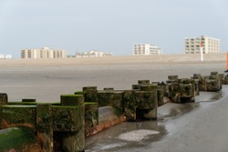 Rusty Outlet Pipe on Beach with Vacation Hotels in Background on New Jersey Shore