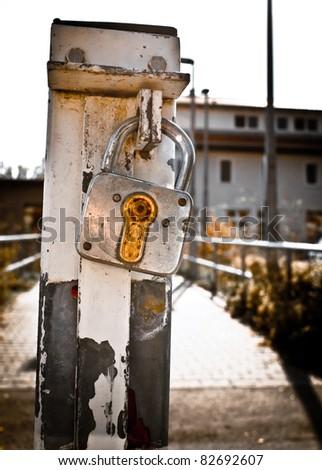 Rusty padlock on a metal pole - stock photo