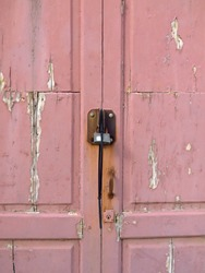 Rusty padlock on pink wooden door with uncorked paint. Old metal padlock on a uncorked wooden door. Old pink door with rusty and spoiled paint.
