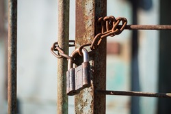 Rusty padlock with chain on a metal gate, prison concept