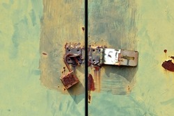 rusty padlock with hasp on grunge green metal door of cabinet under sunlight, damaged steel key padlock that has been weathered and damaged