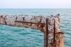 Rusty rebar structure in the cracked old pillar and beam concrete of the harbor bridge at the sea, salty air affect metals with green sea background.