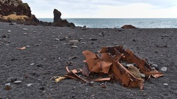 Rusty remains of the wreck of Grimsby fishing trawler Epine (GY7) at Djúpalónssandur beach on west coast of Snæfellsnes peninsula, Iceland with black colored pebble stones and lava rock formations.
