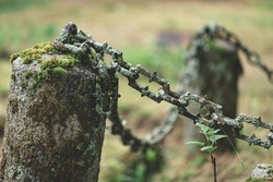 Rusty ring and chain hanging from a granite post bordering a centuries old graveyard