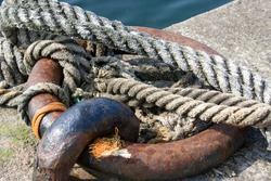 Rusty ring and old ropes on quay