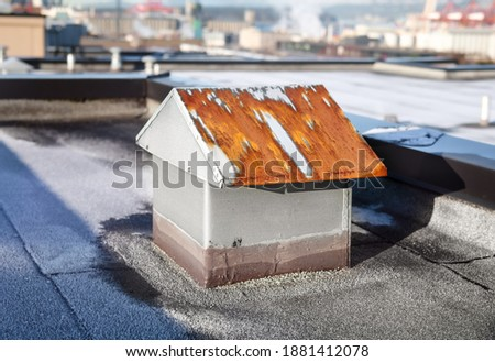 Rusty roof vent in need of repair. Flat roof with 2-ply SBS or modified bitumen roofing system. Custom made metal bathroom or laundry exhaust vent in shape of a tiny house. Selective focus. stock photo