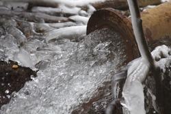 Rusty sewage pipe draining water during winter