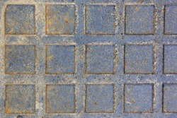 Rusty sewer manhole cover. Geometric pattern on the cover of the sewer manhole. Rusty sewer manhole cover. Close-up view of the texture of the old rusty metal sewer manhole. ?opy space and backdrop