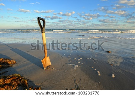 Rusty Shovel in Wet Sand at the Beach. A rusty shovel digging in wet sand along a shoreline under a partly cloudy blue sky.