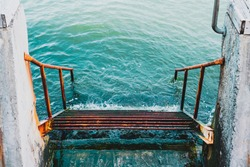 Rusty stairs to the turquoise sea. Old staircase going to water. Empty abandoned ladder near a ocean. Place for relaxation. Outdoor. Nature. Sea shore