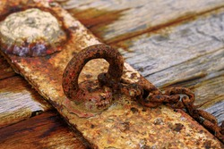 Rusty steel ring and mooring lines in a seaport. Rusty iron chain on the wooden ground.