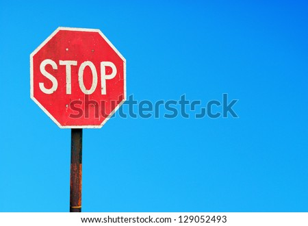 rusty stop sign on a metal pole against a vibrant blue sky (copy-space for your design)