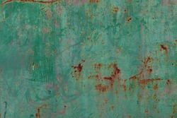 Rusty surface of green metal plate. Rusty texture backdrop. Rust on old metal. Rust on old green fence. Grunge ruststained metal fence. Mildew on green iron-plate fencing.  Seedy bingery paling
