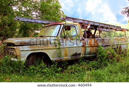 Rusty, vine covered work truck left where it died in the pasture in Kentucky, USA.