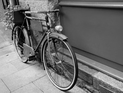 Rusty vintage bicycle leaning on  wooden board (useful for entering a text advertisement, menu etc) and carrying plants in wooden box as decoration. Aged photo. Black and white.