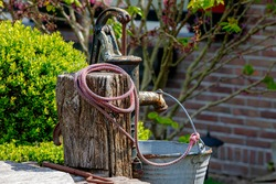 Rusty vintage outdoor rocking groundwater in rural or countryside, Using a pump to draw water out of the ground, Old stainless steel water tank with rope hanging on wooden pole.