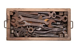 Rusty vintage tools such as wrenches, spanners, pincers and other in a wooden box isolated on white background, top view