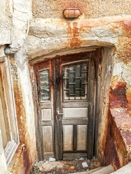 Rusty Wall Sconce Over Weathered Wood Door and Entry