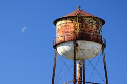 Rusty water tower in a cloudless sky with crescent moon