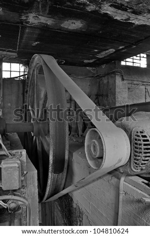 Rusty wheel belt driven machinery in abandoned factory interior. Black and white.