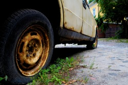 Rusty wheel of an old car in perspective