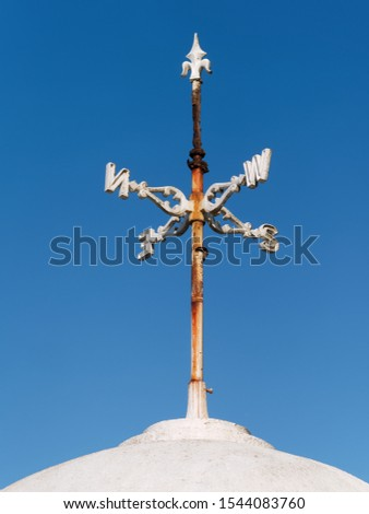 Rusty White Cardinal Direction or Direction pointer Sign against blue sky. Directions North, South, East, West are denoted by their initials N, E, S, and W on the metal plates.