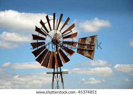 Rusty windmill with clouds in the background