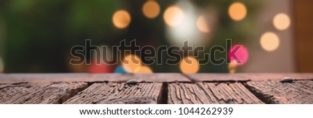 Rusty wooden plank against defocused of christmas tree lights and fireplace #1044262939