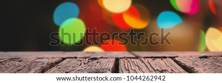 Rusty wooden plank against defocused of christmas tree lights and fireplace #1044262942