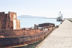 Rusty wreck moored, abandoned in the pier in the harbor of Cagliari Sardinia.