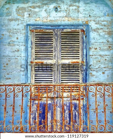rusty wrought Iron balcony in front of a blue painted and cracked old wall with window